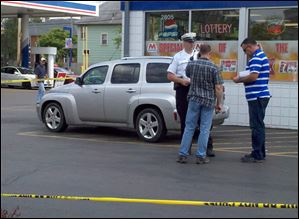 Columbus police and FBI agents stand near a car in a gas station parking lot at the corner of Hague Avenue and Broad Street in Columbus. The car was connected to the disappearance of three teenagers from Putnam County.