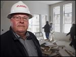 Richard Vap, owner of South Valley Drywall, poses for a photo at a home construction site with one of his crews working in the background in Lakewood, Colo.
