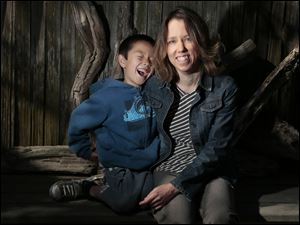 Tara Sievers and her son, Bodhi, 7, pose for portrait at their Belmont Shores home. The City of Long Beach is cutting hours for some part-timers to avoid benefit costs under the federal healthcare law. Longtime parks employee Sievers is affected by this and has complained to city officials about them hurting workers and dodging the new law.