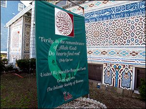 "A banner reading ""United We Stand For Peace on Earth"" stands outside the Islamic Society of Boston mosque in Cambridge, Mass."