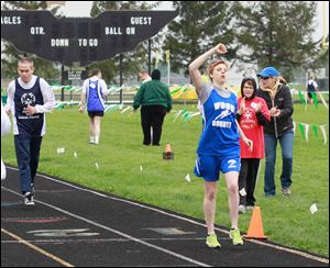 800-meter gold medalist Amanda Gump of Wayne crosses the finish line before Edmund Lyons of Toledo at the Special Olympics Ohio Area 4 competition at Oregon's Clay High School.