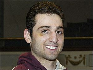 In this file photo, Tamerlan Tsarnaev smiles after accepting the trophy for winning the 2010 New England Golden Gloves Championship in Lowell, Mass.