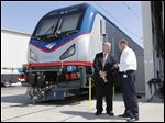 Joseph Boardman, Amtrak President and CEO, left, talks with Michael Cahill, president of Siemens Rail Systems, next to one of the new Amtrak Cities Sprinter Locomotive that was built by Siemens in Sacramento, Calif.  The new electric locomotive will run on the Northeast intercity rail lines and  replace Amtrak locomotives that have been in service for 20 to 30 years.
