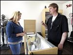 Josh Harris, owner of Smoke Revolt , right, sells flavored e-liquid nicotine to customer Michelle Mikesell, at his shop.
