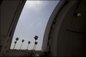 Palm trees are seen through an observatory door at Caltech's Linde + Robinson Laboratory in Pasadena, Calif. A mile above this city, sensors gaze down on the basin from atop Mount Wilson the way a satellite fixates on Earth, collecting pieces of information about Los Angeles' carbon footprint.