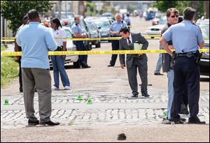 New Orleans police officers investigate at Frenchmen and North Villere streets after gunfire injured 19 at a Mother's Day parade. Police saw three suspects fleeing the area, but no arrests have been made.