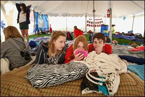 Rachel Phalen, 13, center left, Alexa Borgerson, 13, center, and Luke Kilcorse, 13, take a break and catch up on their television in the District 5 team tent. The 13 teams totaling 130 participants were joined by about 50 volunteers to spend 24 hours together to promote a drug and alcohol-free life.