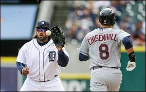 The Tigers' Prince Fielder, left, catches a throw from pitcher Rick Porcello to get the Indians' Lonnie Chisenhall out in the fourth inning of Sunday's 4-3 Cleveland win at Comerica Park.