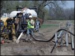 Savoy Energy LP workers install a pipeline in a farm field off  Howell Highway in Adrian. City com­mis­sion­ers signed con­tracts with the firm for oil leases of more than 1,100 acres of city-owned land.