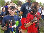 "Brandon Adams, left, and Kenneth Poupard got muddy during the ""Pan­ther Prowl Mud Run,"" a walk-a-thon of sorts held by Wayne Trail Ele­men­tary. Prin­ci­pal Lonny Riv­era said the intent was to boost interest in the annual fund-raiser."