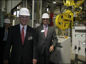 Hiroya Kawasaki, president of Kobe Steel, Ltd., left, and John Surma, president and CEO of U.S. Steel, near the machine that wraps a protective strapping around the completed coil.