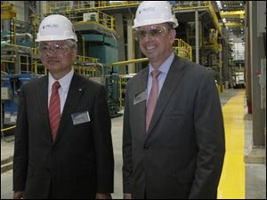 Hiroya Kawasaki, president of Kobe Steel, Ltd., and John Surma, president and CEO of U.S. Steel near the furnace and water quench area of the plant.