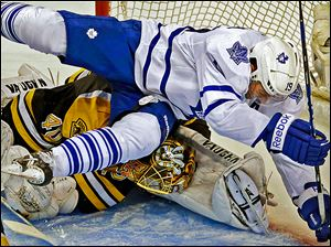 Toronto's Joffrey Lupul bends Boston Bruins goalie Tuukka Rask's head to his leg as he crashes into him in the second period.