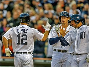 Detroit's Andy Dirks is met at home plate by Don Kelly, center, and Jhonny Peralta, after hitting a grand slam in the fourth inning.