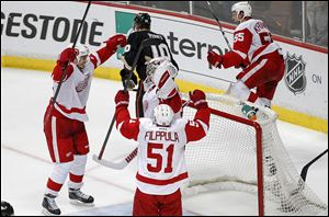 Detroit's Jonathan Ericsson, left, Valtteri Filppula, and Niklas Kronwall celebrate with goaltender Jimmy Howard after defeating Anaheim. The seventh-seeded Wings hope to follow the same path as last year's champions, Los Angeles, which was seeded eighth.