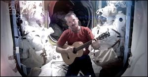 A NASA photo shows astronaut Chris Hadfield recording the first music video from space on Sunday.