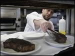 Chef Tim Childers places a 10-ounce filet mignon onto a plate a plate next to a 14-ounce New York strip at Rockwell's.