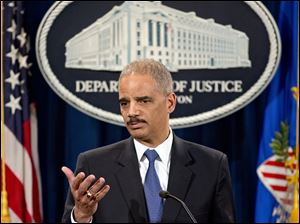 Attorney General Eric Holder is questioned during a news conference today.