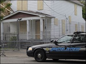 A Cleveland police patrol car sits in front of the boarded up home of Ariel Castro in Cleveland today.