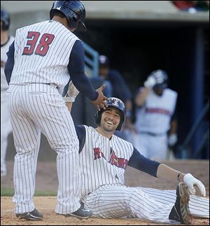 The Hens' Nick Castellanos, seated, celebrates scoring with Ramon Cabrera in the fourth inning.