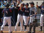 Mud Hens second baseman Brandon Douglas  is congratulated by teammates after hitting a three-run homer in second inning.