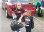 Lourdes student Amanda Borton helped with the cleanup of streets near a Toledo family emergency shelter, and she is with Toledo resident Calvina Giles, 5.