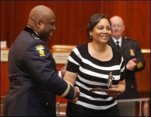 Police Chief Derrick Diggs presents the Civilian Employee of the Year award to Ethel Perry.