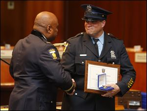 Toledo Police Chief Derrick Diggs, left, presents a Meritorious Service Medal to Officer Mark Johnson during the Toledo Police Department Awards Ceremony at One Government Center today.