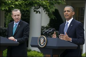 President Obama, accompanied by Turkish Prime Minister Recep Tayyip Erdogan gestures during their joint news conference, today at the White House in Washington.