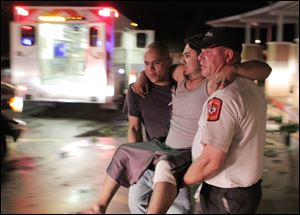 Johnny Ortiz, left, and James South, right, carry Miguel Morales, center, who was injured in a tornado, to an ambulance in Granbury, Texas, Wednesday.