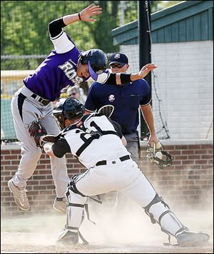 Perrysburg catcher Kyle Durham (21) tags out Fremont Ross' Tyler Wolf at the plate during a Division I sectional baseball game on Thursday in Bowling Green. Perrysburg defeated Fremont 5-3.