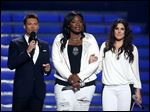 Host Ryan Seacrest, left, and finalists Candice Glover, center, and Kree Harrison speak on stage at the 'American Idol' finale Thursday night.