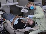 Navy veteran Terry Keller of Toledo receives dental care from Karen Knowles during the fourth annual Stars, Stripes and Smiles event at Hires Dental Care in Toledo.