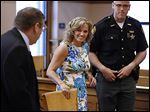 Terri Camp Kruse leaves Ottawa County Common Pleas Court on Friday with her attorney, William Hayes, left, after being granted limited driving privileges by Judge Bruce Winters.