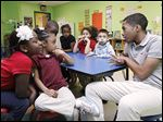 Donovan Vaughn, 15,  interacts with students at the Creative Village Child Devel-opment Center in Toledo as part of the Student African American Brotherhood.