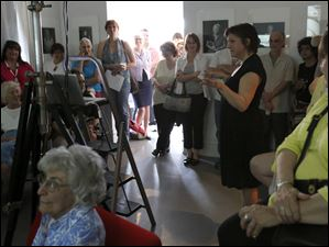 Gallery co-owner Paula Baldoni, center right, introduces speaker Matika Wilbur for a lecture on Wilbur's photographic work at the River House Arts Gallery Thursday, May 16, 2013 in Perrysburg.