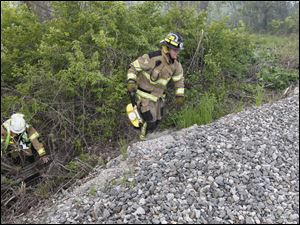 Monroe Township firefighters had a hard time finding a route to reach the marsh fire in Monroe, Mich. They had to traverse through woods and over railroad tracks.