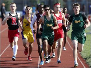 Corey Fink, left, of Rogers High School wins the 1600 meter run.