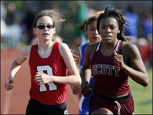 Becca Lustic, left,  of Rogers High School passes Mya Barnhill of Scott High School to win the 1600 meter run.