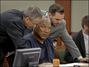 O.J. Simpson, center, talks with defense attorneys Ozzie Fumo, left, and Josh Barry during an evidentiary hearing in Clark County District Court, Thursday in Las Vegas.