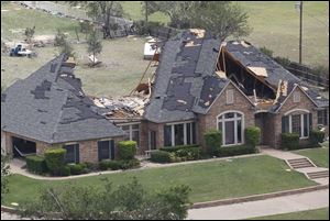 A home in Cleburne, Texas has portions of its roof missing Thursday. Ten tornadoes touched down in several small communities in North Texas overnight, leaving at least six people dead, dozens injured and hundreds homeless.