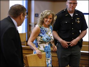 Terri Camp Kruse of Oak Harbor smiles at attorney William Hayes after being granted limited driving privileges by Judge Bruce Winters during a hearing in Ottawa County Common Pleas Court today.