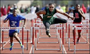 Dionte Carey of Start defeats DeMarkus Darrington of Woodward in the City League track meet on Friday night. Carey's big night led the Spartans to the team title.