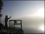 Terry Van Bibber, Toledo, casts his line out into the Maumee River as fog envelops the area.