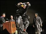 Zander Epps of San Diego jumps as he crosses the stage to receive his bachelor's degree in interdisciplinary studies during Lourdes University's commencement ceremony.