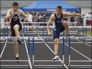 Dustin Preble, right, wins his heat in the 300 hurdles.
