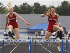 Eastwood's Megan Selhorst, left, is 2nd and teammate Allison Sutton wins the 1st heat of the 300 meter hurdles.
