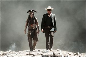 This undated publicity photo released by Disney/Bruckheimer Films shows, from left, Johnny Depp as Tonto and Armie Hammer as The Lone Ranger, in a scene from the movie,