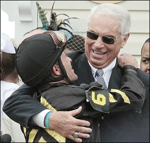 Jockey Gary Stevens, left, embraces trainer D. Wayne Lukas in the winner's circle after Oxbow gave Lukas his 14th win in a Triple Crown race. It was Stevens' first Triple Crown victory since 2001.
