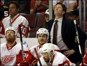Detroit Red Wings head coach Mike Babcock, rear right, looks up a scoreboard during the first period today in Chicago.